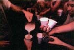 Students at a fraternity party crowd around a pitcher of beer. Binge drinking, or having several drinks in a row for the purpose of getting drunk, has become a growing problem on college campuses. Its effects can be serious, including alcohol poisoning, coma, and even death. The Image Works