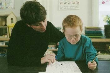 A boy with ADHD receives one-on-one instruction with his teacher. The method of teaching a child according to his or her own special way of learning is an effective way of managing ADHD. Photo Researchers, Inc.