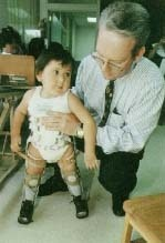 A doctor examines a child with spina bifida at a clinic near the Texas-Mexico border. The child's disorder is believed to have been caused by pollution in the area. Annie Griffiths Belt/Corbis